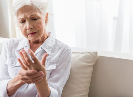 Senior woman suffering from arthritis pain rubbing her hand.