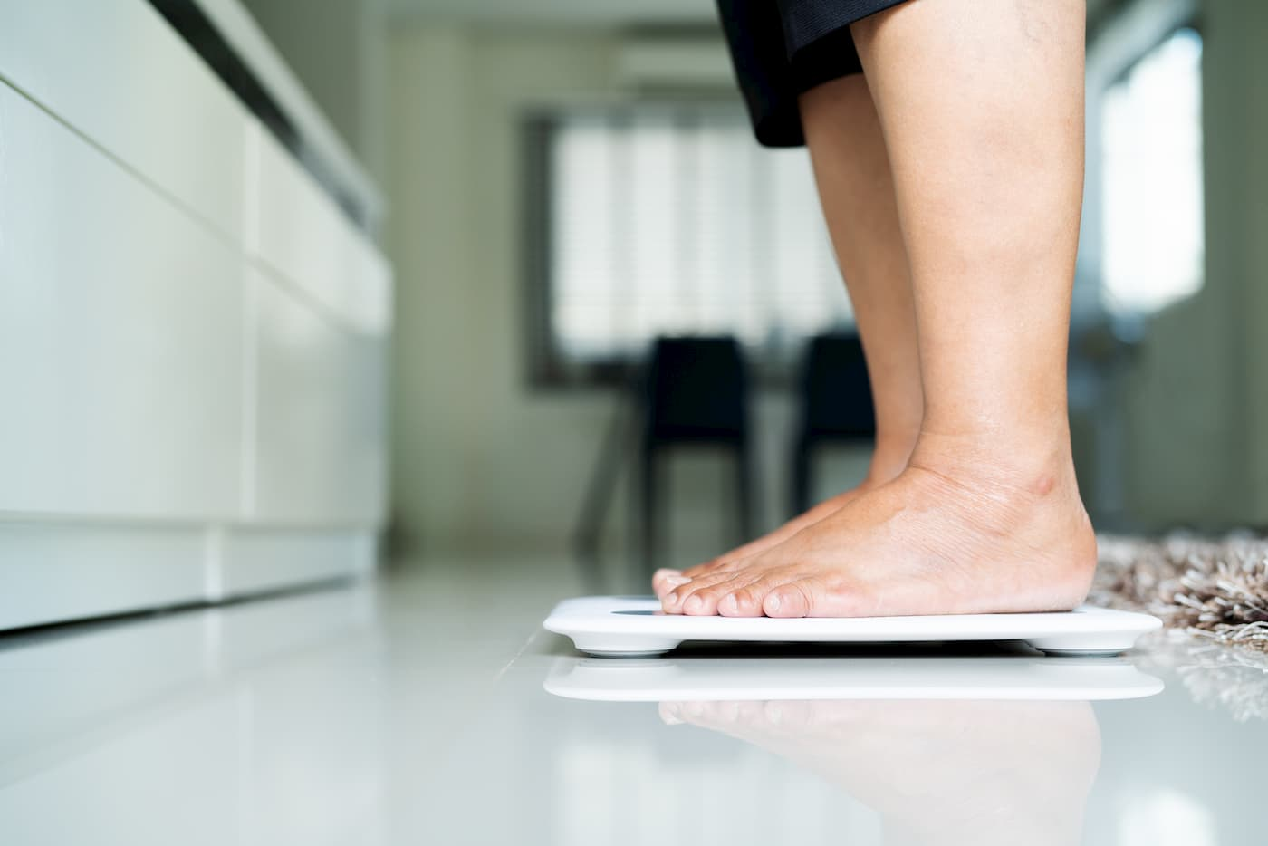 A senior standing on a scale as they work to maintain a healthy weight.