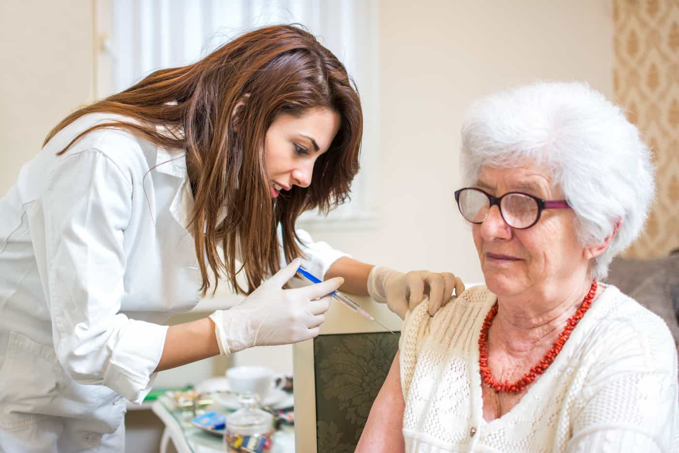 Senior receiving her influenza vaccination from a healthcare provider