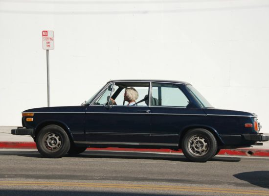 An older woman driving a vintage car.