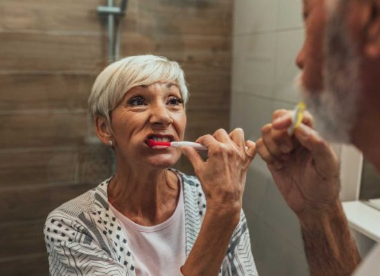 Two older adults practicing good dental hygiene
